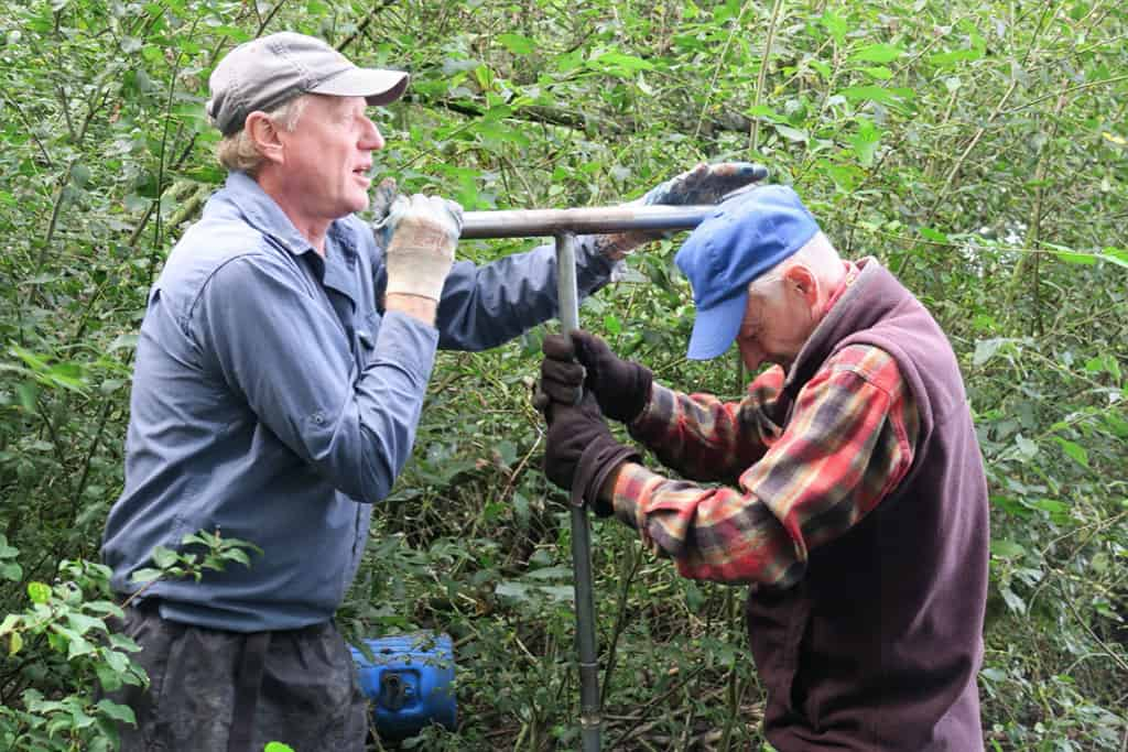 Warren Eastwood and volunteer Fred Porton tackle the auger at a pond belonging to volunteer Don Evans of Norton Canon